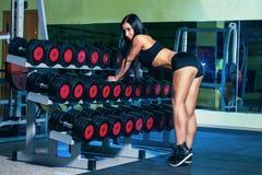 De sexy vrouw die van Nice training met domoren in gymnastiek doen Stock Foto's