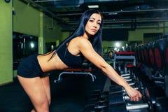 De sexy vrouw die van Nice training met domoren in gymnastiek doen Royalty-vrije Stock Afbeeldingen