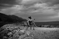 De sexy vrouw of het meisje met wijnglas zitten op bank openlucht over donkere schemeringhemel met wolken op strand met overzees  Royalty-vrije Stock Fotografie