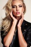 De sexy vrouw met blonde haar en avondmake-up, draagt leerjasje Stock Fotografie