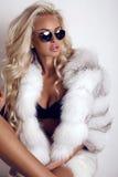 De sexy vrouw met lang blond haar draagt luxuriosbontjas en zonnebril stock foto's