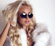 De sexy vrouw met lang blond haar draagt luxuriosbontjas en zonnebril royalty-vrije stock foto's