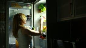 De sexy Vrouw opent de ijskast bij nacht selecteert een komkommer stock footage