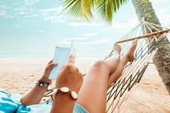 De sexy vrouwen zonnebaden ontspannen en lezing een boek op hangmat Royalty-vrije Stock Foto
