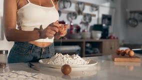 De sexy vrouwenkoks bij de keuken, vrouw breekt het ei aan het deeg, makend het deeg, de bakkerij en het brood stock video