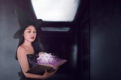 De sexy werktijd van de heksenvrouw met het boek in de donkere ruimte Royalty-vrije Stock Fotografie