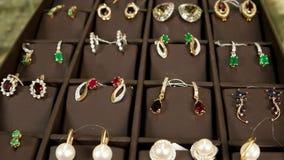 De showcase met juwelenoorringen met edelstenen, Juwelen op opslagvertoning, Gouden juwelen voor vrouw, stelde bloot voor stock videobeelden