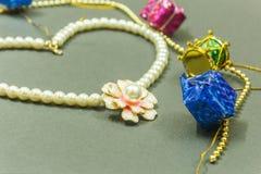 De showcase van Ivoor kleurde gemhalsband met bloem gevormde tegenhanger en oorringen op een donkere achtergrond Met selectieve n Royalty-vrije Stock Afbeelding