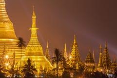 De Shwedagonpagode bij nacht met schijnwerper wijst op gouden oppervlakte van de pagode Stock Foto