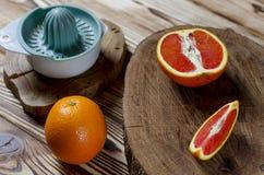 De Siciliaanse sinaasappelen en het mes met zwarte knop rusten op een houten raad, die zich op een houten lijst bevindt stock fotografie