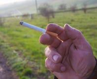 De sigaret is in de hand van de mens. Stock Fotografie
