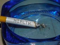 De sigaret overtreedt Gezondheidsconcept met Gezondheid schrijvend op een sigaret stock afbeeldingen