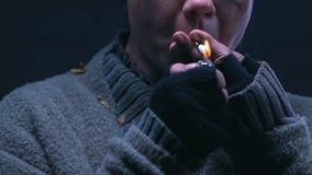 De sigaret van de bedelaarsverlichting, het roken verslaving onder dakloze mensen, close-up stock footage