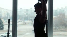 De silhouetatleet heft barbell in gymnastiek op stock videobeelden
