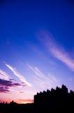 De silhouetbouw onder de zonsonderganghemel stock afbeeldingen