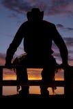 De silhouetcowboy zit omheining royalty-vrije stock fotografie