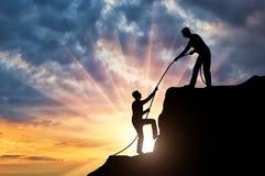 De silhouetklimmer helpt om de bovenkant van een andere klimmer te beklimmen, die hem werpen een kabel stock afbeeldingen