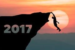 De silhouetmens beklimt in klip aan doel het plaatsen van woord Gelukkig Nieuwjaar 2017 met zonsondergang op achtergrond Royalty-vrije Stock Foto
