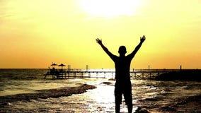 De silhouetmens bidt aan God in Dawn op het Strand, Mens met Zijn Handen omhoog bij Zonsondergang stock video