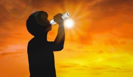 De silhouetmens is drinkwaterfles op hete weerachtergrond met zomer Concept op hoge temperatuur en hittegolf royalty-vrije stock afbeelding