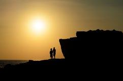 De silhouetmensen bekijken zonsondergang van berg Royalty-vrije Stock Fotografie