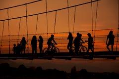 De silhouetmensen die op kabel lopen overbruggen Stock Fotografie