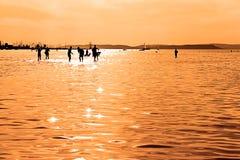 De silhouetten die van kinderen in Meer Balaton spelen Royalty-vrije Stock Foto