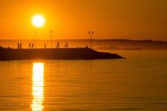De silhouetten en de zonsondergang van mensen Stock Foto