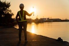 De silhouetten van Aziatische de holding van de vrouweningenieur moersleutels en status op scheepswerf en achtergrond is de silo  royalty-vrije stock foto