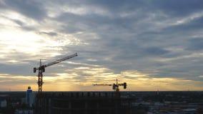 De silhouetten van bouwkranen over de verbazende samenvatting van de zonsonderganghemel stock video