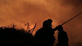 De silhouetten van brandbestrijders doven brand stock video
