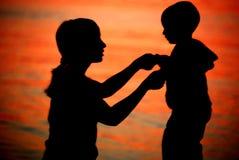 De silhouetten van de moeder en van de zoon Stock Foto