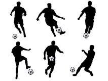 De silhouetten van de voetballer Stock Foto's