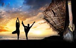 De silhouetten van de yoga op het strand Stock Afbeeldingen