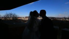 De silhouetten van gelukkig jonggehuwde koppelen teder het kussen op het balkon bij de achtergrond van het stadspanorama moving stock footage