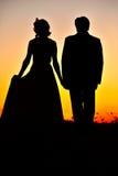 De silhouetten van het paar in de zonsondergang Stock Afbeeldingen