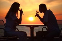 De silhouetten van het paar op zonsondergang achter lijst Royalty-vrije Stock Afbeeldingen