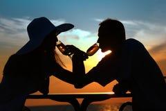 De silhouetten van het paar op zonsondergang drinken van glazen Stock Foto