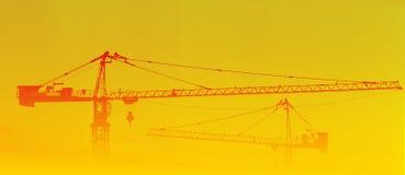 De silhouetten van kranen in zonsopgang en mist Stock Foto