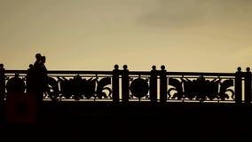De silhouetten van mensen gaan over de brug stock footage