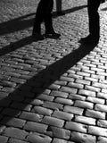 De silhouetten van mensen op cobblestoned straat royalty-vrije stock afbeeldingen