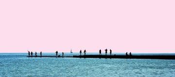 De silhouetten van mensen op een golfbreker Royalty-vrije Stock Foto
