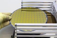 De siliciumwafeltjes in de doos van de staalhouder nemen indienen uit langs handschoenena wafeltje is een dunne plak van halfgele stock afbeelding