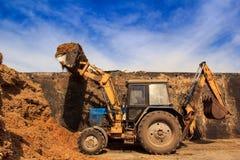 De silo-lader tractor heft gietlepel met silo in diepe silogeul op Stock Foto's