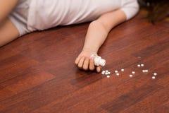 De simulatie van de misdaadscène. Overdosedmeisje dat op de vloer ligt Royalty-vrije Stock Foto