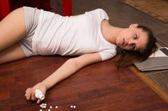 De simulatie van de misdaadscène. Overdosedmeisje dat op de vloer ligt Royalty-vrije Stock Afbeelding