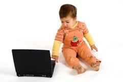 De sinaasappel kleedde verbaasde jongen die aan laptop werkt Royalty-vrije Stock Foto's