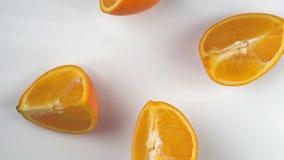 De sinaasappel valt en verbrijzelt in plakken, langzame motie, witte achtergrond stock video