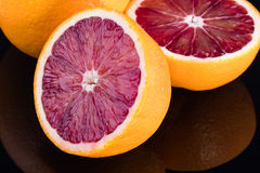 De sinaasappel van het besnoeiingsbloed op een zwarte achtergrond Stock Foto
