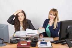 De situatie in het bureau - één werknemer het letten op omslagen met documenten en clutched haar hoofd, en de tweede bekijkt lapt Royalty-vrije Stock Fotografie